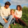 Family from mother, father and daughter sits on green hill in park — Stock Video