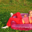 Girl sit in children's inflatable armchair, holds finger in mouth and smile - Foto de Stock