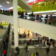 Shoppers on escalators in big multistory mall - Stock Photo