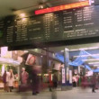 Stock Video: Board with departure of trains, passengers in station building in Paris