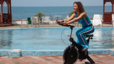 Happy young woman training on exercise bicycle, pool and sea in background — Stock Video