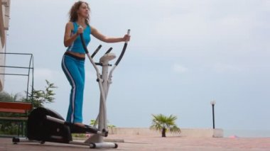 Happy young curly-headed woman on training apparatus outdoor — Stock Video