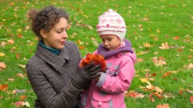 Young woman with little girl gathering autumn maple leaves — Stock Video