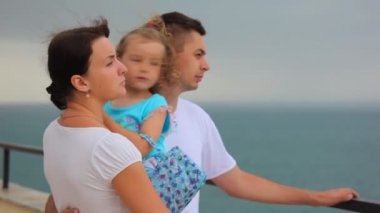 Standing family with little girl in mother's hands looks at sea — Stock Video