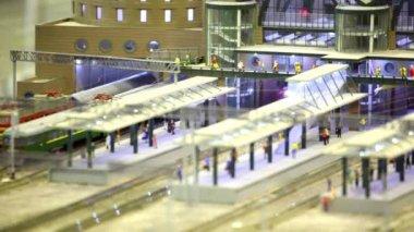 En la ciudad de juguete moderno tren de pasajero pasa a través de la plataforma en la estación de tren — Vídeo de stock