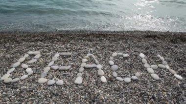 BEACH inscription from stones in pebble beach with sea surf — Stock Video
