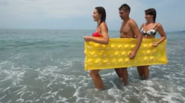 Two womans and man holds inflatable mattress walking on beach — Stock Video