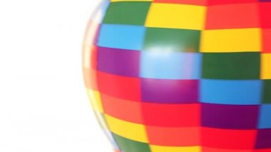Part of coloured toy air ball revolves fast on white background — Stock video