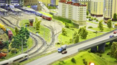 En la ciudad de juguete moderno tren pasa por ferrocarril para entrenar a parque entre casas y árboles — Vídeo de stock