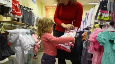 Mother with her little daughter buying children's clothes — Vídeo Stock