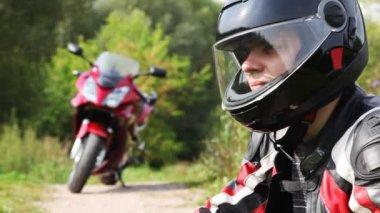 Biker sit down on motorcycle and close visor on it helmet — Stock Video