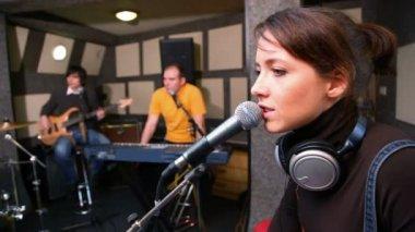Mladá žena zpívá přes mikrofon v studio — Stock video