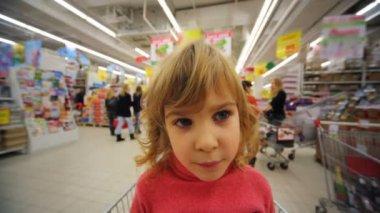 スーパー マーケットのトロリーをショッピングに座っている小さな女の子 — ストックビデオ
