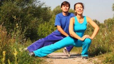 Homme et femme effectue des exercices sur le chemin d'accès au parc ensemble — Vidéo