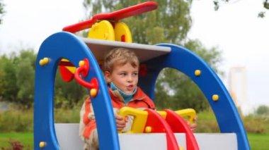 Ung pojke svänga i leksak helikopter i lekplats — Stockvideo