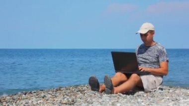человек с ноутбуком сидя на галечный пляж, море в фоновом режиме — Стоковое видео