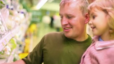 Smiling man with little girl buying parsley in supermarket — Stock Video