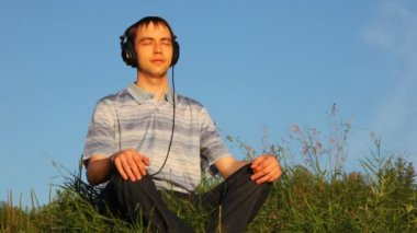 Young man sits listening to music in cutephone on glade in park in summer — Stockvideo