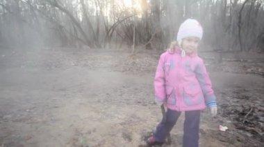 Bambina con in piedi bastone vicino tombino di fogna fumante — Video Stock