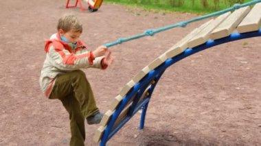 Mladík dostane na snímku pomocí kabelu v dětské hřiště — Stock video