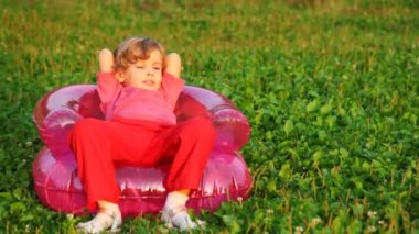 Girl rest in children's inflatable armchair on field in park — Stockvideo
