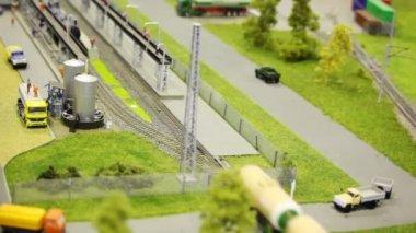 Zug schiebt tankwagen auf schiene im modernen spielzeug stadt zur tankstelle zu straßen mit kleinen autos und bäumen — Stockvideo