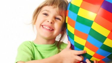 Girl embraces toy varicoloured air ball and smile on white background — Stock Video