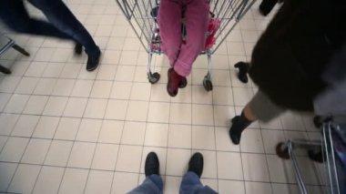 Comprador com câmera e carrinho de compras vai no shopping, ver no chão — Vídeo Stock