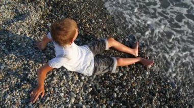 Young boy sits on pebble beach and looks at sea, top view — Stock Video