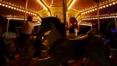 Kids on carousel merry-go-round amusement ride with galloping horses — Stock Video