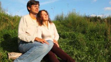 Pareja se sienta cerca de hierba verde, hablar y sonreir en parque en verano — Vídeo de Stock