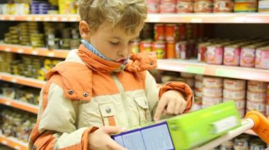 Young boy reading inscription on goods box in supermarket — Stock Video