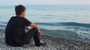 Teenager sits on pebble beach and looks at sea, back view — Stock Video
