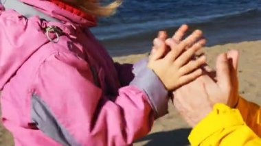 Daughter and father play, clap together in palms on coastline of river — Stock Video