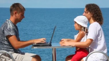 Happy family of three persons sits at table with notebook, sea in background — Stock Video