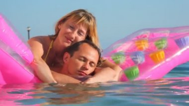 Man and woman embracing on inflatable mattress in swimming pool — Stockvideo