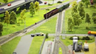 Train pushes freight cars on rail in modern toy city among roads and trees — 图库视频影像