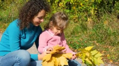 Young woman with little girl take a good look at maple leaves — Stock Video