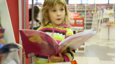 Surprised little cute girl looking at child's book in bookshop — Vídeo Stock