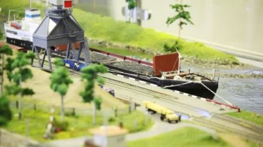 Toy train bring empty cargo wagon on rail to storage station in port near transport ship — Stock Video