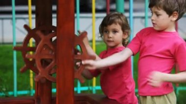 Boy and girl in crimson vests twist handles of an artificial well — Stock Video