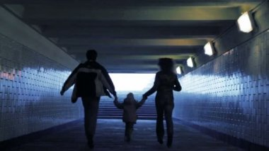 Family of three persons running in underground passage from camera, joined hands — Stock Video