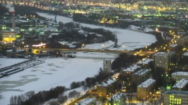 The top view on a winter city, on centre the frozen river. Gradually darkens. Time lapse. — Stock Video