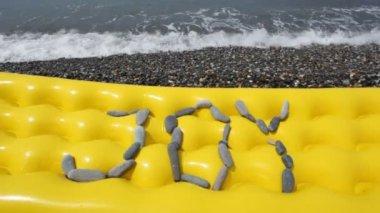 Joy nápis z kamenů v oblázkovou pláž s mořem surf — Stock video