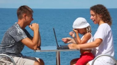 Happy family of three persons with notebook sits at table, sea in background — Stock Video