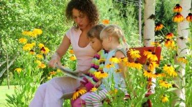 Matka čtení s dvěma dívkami na lavičce na zahradě — Stock video