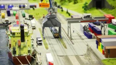 In modern toy city train bring tank-wagon on rail to storage station in port near transport ship — Stock Video