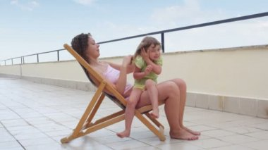 Young woman sitting on high chair outdoor and combing hair her little daughter — Stock Video