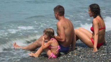 Family of three persons sits on beach under sea surf wave, side view — Stock Video