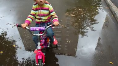 Little girl sits on bicycle on wet asphalt with puddles, camera moving around — Stock Video